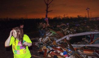 In this Sunday, April 27, 2014 photo, Lauren Watts searches for her dog in Mayflower, Ark., after a tornado struck the town. A tornado system ripped through several states in the central U.S. and left more than a dozen dead in a violent start to this year's storm season, officials said. (AP Photo/The Arkansas Democrat-Gazette, Benjamin Krain)  ARKANSAS TIMES OUT; ARKANSAS BUSINESS OUT