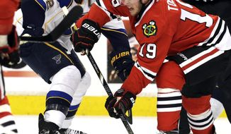 Chicago Blackhawks' Jonathan Toews (19) passes the puck against St. Louis Blues' David Backes (42) during the first period in Game 6 of a first-round NHL hockey playoff series in Chicago, Sunday, April 27, 2014. The Blackhawks won 5-1. (AP Photo/Nam Y. Huh)