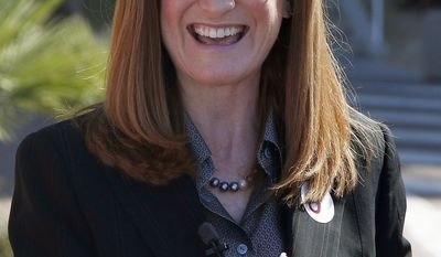 """Christine Jones, a former legal counsel for the website hosting company GoDaddy, gives a thumbs up after she filed her nominating petitions to enter the Republican primary for Arizona governor for the August primary on Monday, April 28, 2014, in Phoenix. Jones is running without public funding and called herself an """"unapologetic conservative"""" who will fight for gun rights, border security, and to eliminate federal intrusion into school policy. (AP Photo/Ross D. Franklin)"""