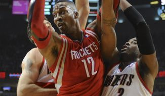 Houston Rockets' Dwight Howard (12) is trapped by Portland Trail Blazers' Wesley Matthews (2) and Joel Freeland during the first half of game four of an NBA basketball first-round playoff series game in Portland, Ore., Sunday March 30, 2014. (AP Photo/Greg Wahl-Stephens)