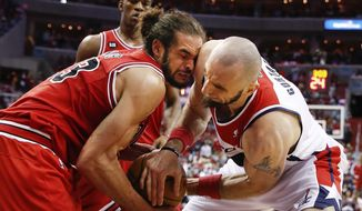 Chicago Bulls center Joakim Noah, left, and Washington Wizards center Marcin Gortat, right, from Poland, battle for control of the ball during the second half of Game 4 of an opening-round NBA basketball playoff series in Washington, Sunday, April 27, 2014. The Wizards defeated the Bulls 98-89. (AP Photo/Alex Brandon)