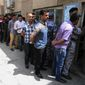 Iraqi security forces line up outside a polling center in Baghdad on Monday, two days before the civilian population votes. Despite democratic elections, Baghdad is gripped by fear and scarred by violence more than two years after the U.S. withdrawal of troops. (Associated Press photographs)