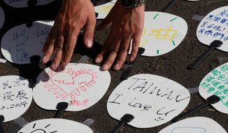 A student protester against a trade pact with China organizes paper fans with notes of support outside the legislature in Taipei, Taiwan, Thursday, April 10, 2014. Students evacuated the legislature Thursday night after forcefully occupying it for the last three weeks in protest to a trade pact with China, challenging the president's policy of moving the democratic island economically closer to China. (AP Photo/Wally Santana)