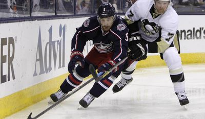 Columbus Blue Jackets' Jack Skille, left, tries to carry the puck past Pittsburgh Penguins' Paul Martin during the second period of Game 6 of a first-round NHL playoff hockey series Monday, April 28, 2014, in Columbus, Ohio. (AP Photo/Jay LaPrete)