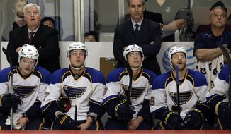 St. Louis Blues head coach Ken Hitchcock, top left, and his players look at the scoreboard after Chicago Blackhawks' Duncan Keith scored during the third period in Game 6 of a first-round NHL hockey playoff series in Chicago, Sunday, April 27, 2014. The Blackhawks won 5-1. (AP Photo/Nam Y. Huh)