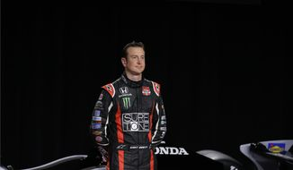 NASCAR driver Kurt Busch stands in front of his newly unveiled IndyCar entry for the Indianapolis 500 during an announcement in Indianapolis, Monday, April 28, 2014. Busch will try to be the first driver in a decade to compete in IndyCar's Indianapolis 500 and Sprint Cup's Coca-Cola 600 on the same day. (AP Photo/Michael Conroy)