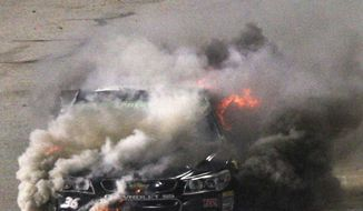 Reed Sorenson's car burns on pit row during the NASCAR Sprint Cup auto race at Richmond International Raceway in Richmond, Va., Saturday April 26, 2014. (AP Photo/Richmond Times-Dispatch, Dan Currier)