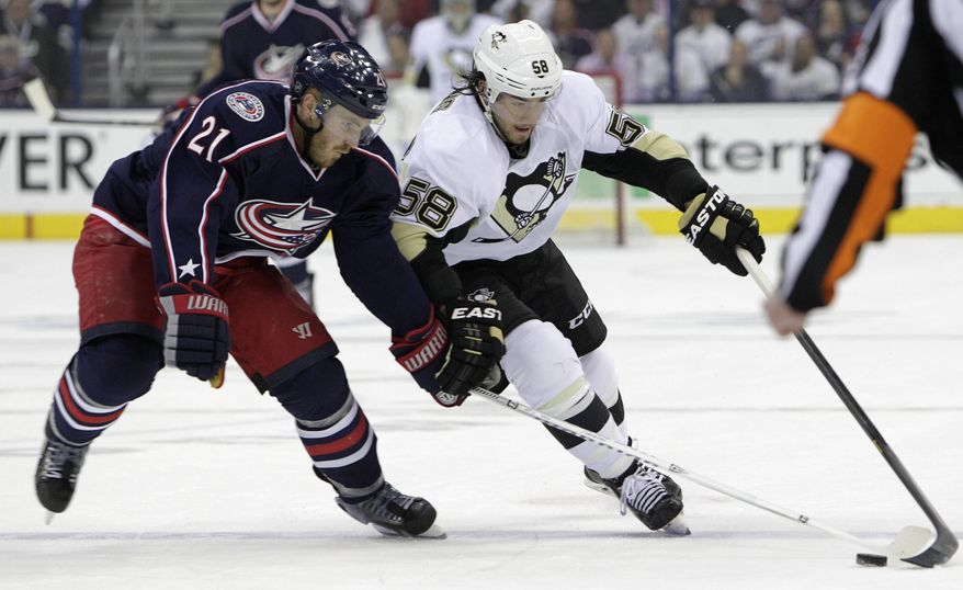 Pittsburgh Penguins' Kris Letang, right, and Columbus Blue Jackets' James Wisniewski chase a loose puck during the first period of Game 6 of a first-round NHL playoff hockey series Monday, April 28, 2014, in Columbus, Ohio. (AP Photo/Jay LaPrete)