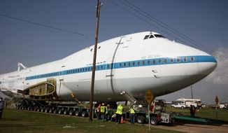 The Boeing 747 Shuttle Carrier Aircraft makes its way under power lines at Ellington Field, Monday, April 28, 2014, in Conroe, Texas. The power poles had to be extended for the plane to fit under. It will travel at least two nights to the Space Center Houston. (AP Photo/Conroe Courier, Kar R Hlava)