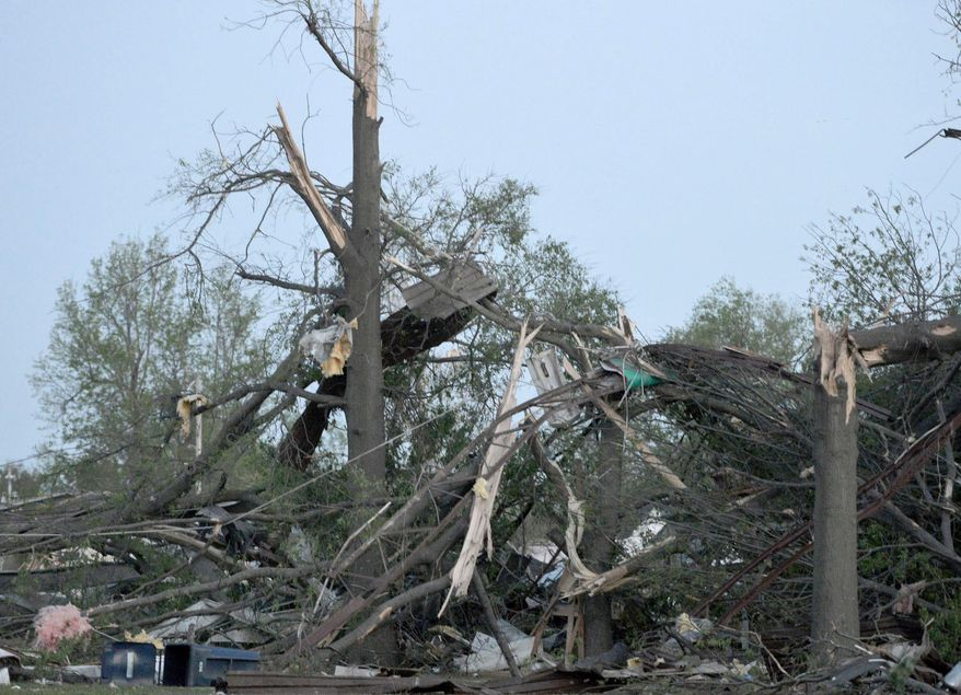 Twisted trees and power lines remain in a residential block near Military Avenue following  the tornado in Baxter Springs, Kan., Sunday, April 27, 2014.  A powerful storm system rumbled through the central and southern United States on Sunday, spawning a massive tornado that  carved through Little Rock's northern suburbs and another that hit Oklahoma and Kansas. (AP Photo/The Joplin Globe, Roger Nomer )