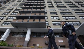 In this Tuesday, April 15, 2014 photograph, Camden County Metro police officers Lucas Murray, left, and Daniel Torres patrol outside the high-rise apartment building, Northgate I, in Camden, N.J. Camden disbanded its police department on May 1 and handed patrols over to the new Camden County-run department that promised more officers for the same cost, largely because it could shed provisions of a union contract that officials saw as onerous. The new department says crime dropped sharply in every category except arson in the first three months of this year, when the new department had enough officers for intense patrols in every neighborhood. (AP Photo/Mel Evans)