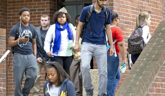 Students evacuate  Marteena Hall as North Carolina A&T State University canceled classes Monday, April 28, 2014 and locked down some buildings while police searched for a man who was reported to be carrying a rifle on campus, in Greensboro, N.C. The lockdown was lifted after a search failed to find any sign of the reported gunman. (AP Photo/News & Record, at North Carolina A&T State University)