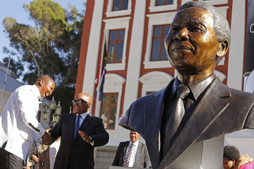 ** FILE ** South African President Jacob Zuma, second left, talks with Mandla Mandela, left, after they and other dignitaries unveiled a bust of former South African President Nelson Mandela, right, at the South African Parliament in Cape Town, South Africa, Monday, April 28, 2014. (AP Photo/Schalk van Zuydam)
