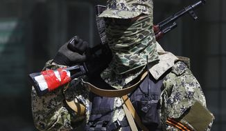 A pro-Russian masked armed man guards at the city hall in Kostyantynivka, 35 kilometers (22 miles) south of Slovyansk, eastern Ukraine, Monday, April 28, 2014, after masked militants with automatic weapons seized the hall building. (AP Photo/Sergei Grits)