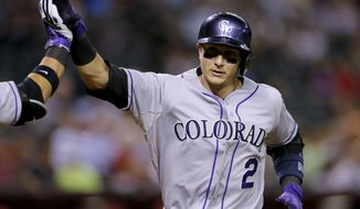 Colorado Rockies' Troy Tulowitzki, left, rounds the bases after hitting a solo home run against the Arizona Diamondbacks during the sixth inning of a baseball game on Monday, April 28, 2014, in Phoenix. (AP Photo/Matt York)