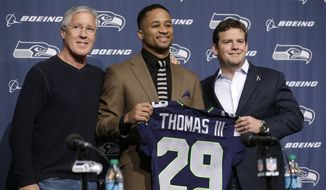 Seattle Seahawks' Earl Thomas, center, stands with head coach Pete Carroll, left, and general manager John Schneider to pose for a photo before beginning a news conference Tuesday, April 29, 2014, in Renton, Wash. The Seahawks announced a four-year extension with the All-Pro free safety, making him the highest-paid safety in the NFL. The deal is worth $40 million over four years and will keep Thomas in a Seahawks uniform through the 2018 season. (AP Photo/Elaine Thompson)