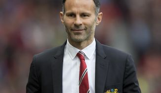 Manchester United's interim manager Ryan Giggs smiles as he takes to the touchline before his team's English Premier League soccer match against Norwich City at Old Trafford Stadium, Manchester, England, Saturday April 26, 2014. (AP Photo/Jon Super)
