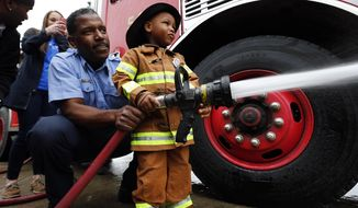 Tyren Johnson, 3, of Detroit, shoots a fire hose with the help of Sgt. Reginald Harper during his wish to be a fireman at Detroit Fire Department Engine 54 in Detroit, Tuesday, April 29, 2014. Make-A-Wish Michigan is celebrating World Wish Day by granting Johnson, who had a heart transplant, his wish. (AP Photo)