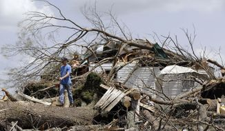 Mike Self helps to cut up trees Tuesday, April 29, 2014, that destroyed a home in Fayetteville, Tenn., when storms came through Monday.  On Sunday evening, roughly 15 tornadoes carved a path of destruction in the South and the country's midsection, according to estimates from the National Oceanic and Atmospheric Administration's Storm Prediction Center. On Monday, around 50 tornadoes ravaged the South, the agency said.  (AP Photo/Mark Humphrey)