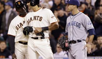 San Francisco Giants' Michael Morse, center, gets a pat on the shoulder from first base coach Roberto Kelly, next to San Diego Padres first baseman Tommy Medica, after Morse's two-run single during the fourth inning of a baseball game Monday, April 28, 2014, in San Francisco. (AP Photo/Marcio Jose Sanchez)