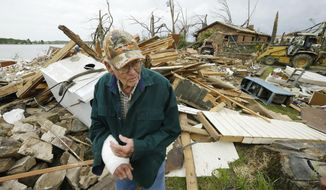 Louie Short walks through rubble that is all that is left of his Mayflower, Ark., home Tuesday, April 29, 2014. Shorts arm was injured in an April 27, tornado struck his neighborhood killing one man.  A dangerous storm system that spawned a chain of deadly tornadoes over three days flattened homes and businesses, forced frightened residents in more than half a dozen states to take cover and left tens of thousands in the dark Tuesday morning. (AP Photo/Danny Johnston)