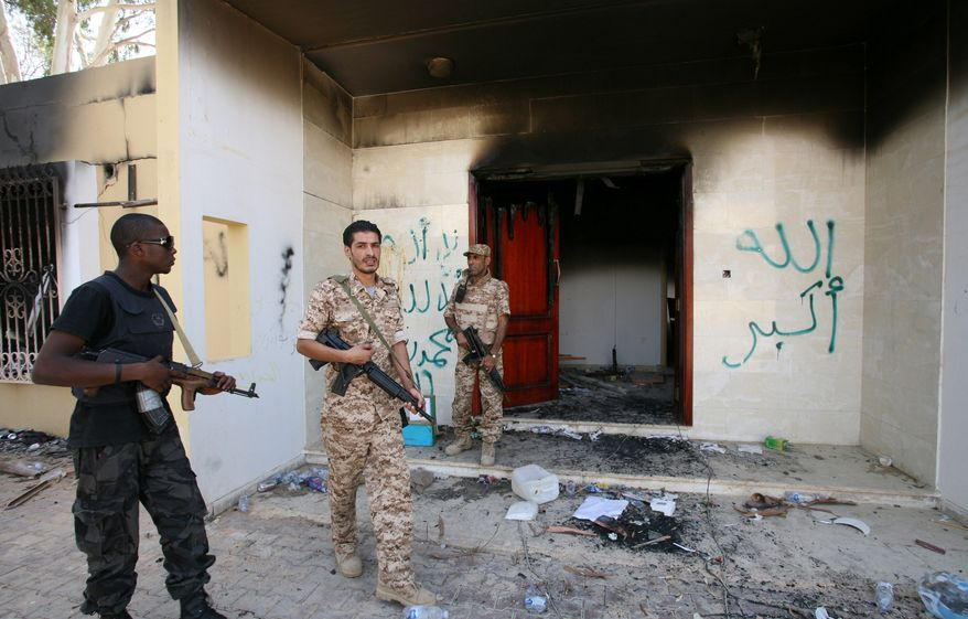** FILE ** In this Sept. 14, 2012, file photo, Libyan military guards check one of the U.S. Consulate's burnt-out buildings during a visit by Libyan President Mohammed el-Megarif, not shown, to the U.S. Consulate to express sympathy for the death of the American ambassador, J. Christopher Stevens and his colleagues in the deadly attack on the Consulate in Benghazi, Libya. (AP Photo/Mohammad Hannon)
