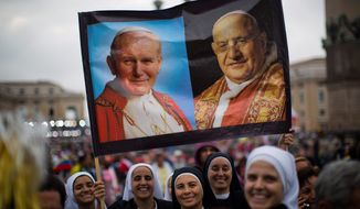 Nuns hold up a poster with portraits of Pope John Paul II, left, and John XXIII, in St. Peter's Square at the Vatican Sunday, April 27, 2014. Pope Francis has declared his two predecessors John XXIII and John Paul II saints in an unprecedented canonization ceremony made even more historic by the presence of retired Pope Benedict XVI. (AP Photo/Emilio Morenatti)