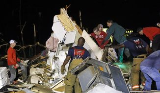 Emergency personnel search the remains of several mobile homes in Louisville, Miss., for survivors early Tuesday morning, April 29, 2014 after a tornado hit the east Mississippi community Monday.  Tornadoes flattened homes and businesses, flipped trucks over on highways and bent telephone poles into 45-degree angles as they barreled through Alabama and Mississippi on Monday, part of a storm system that killed at least nine people in the South and brought the overall death toll from two days of severe weather in the country to at least 26. (AP Photo/Rogelio V. Solis)
