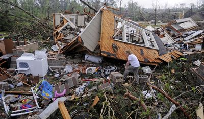 Kevin Barnes searches the remains of his home on Clayton Avenue in Tupelo, Miss., Tuesday, April 29, 2014.  A dangerous storm system that spawned a chain of deadly tornadoes over three days flattened homes and businesses, forced frightened residents in more than half a dozen states to take cover and left tens of thousands in the dark Tuesday. (AP Photo/Thomas Graning)