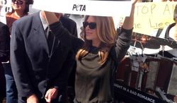 "Jillian Michaels, from ""The Biggest Loser,"" holds up a sign on City Hall steps at a PETA-sponsored rally protesting horse carriages, in New York.  The mayor, Bill de Blasio, also supports banning the carriages. (AP Photo/Jonathan Lemire)"