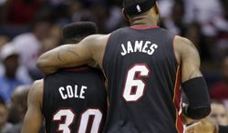 Miami Heat's LeBron James (6) hugs Norris Cole (30) as they walk to the bench during a timeout in the second half in Game 4 of an opening-round NBA basketball playoff series against the Charlotte Bobcats in Charlotte, N.C., Monday, April 28, 2014. The Heat won 109-98, and swept the series. (AP Photo/Chuck Burton)
