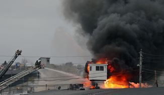 Fire continues to burn in a building at Suffolk Downs race track in Revere, Mass., on Tuesday, April 29, 2014.  The chief operating officer of Suffolk Downs race track says there have been no injuries reported to people or horses in a kitchen building fire. (AP Photo/The Boston Herald,Mark Garfinkel)  BOSTON GLOBE OUT; METRO BOSTON OUT; MAGS OUT; ONLINE OUT