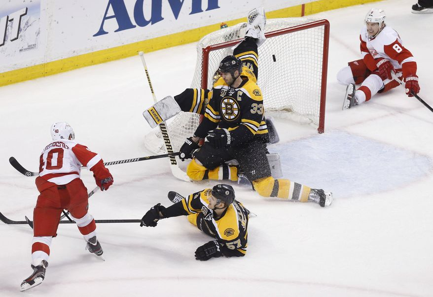 Detroit Red Wings' Henrik Zetterberg (40) scores past Boston Bruins' Tuukka Rask, behind center, during the third period in Game 5 in the first round of the NHL hockey Stanley Cup playoffs in Boston, Saturday, April 26, 2014. Boston won 4-2 and eliminated the Red Wings from the playoffs. (AP Photo/Michael Dwyer)