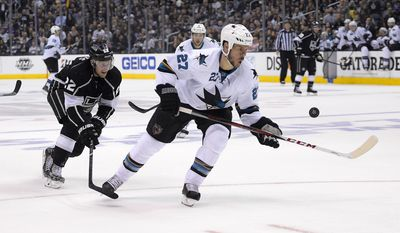 Los Angeles Kings center Trevor Lewis, left, and San Jose Sharks defenseman Scott Hannan vie for the puck during the second period in Game 6 of an NHL hockey first-round playoff series, Monday, April 28, 2014, in Los Angeles. (AP Photo)