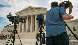 FILE - This April 22, 2104 file photo shows videojournalists setting up outside the Supreme Court in Washington. The court said Monday it will hear the case of a Florida fisherman who wants the court to throw out his conviction for getting rid of some small grouper under a federal law originally aimed at the accounting industry. Commercial fishing boat captain John Yates argues that the federal government used its mighty power to convict him of tossing overboard three fish that were under the 20-inch minimum legal size for red grouper caught in the Gulf of Mexico.  (AP Photo/J. David Ake, File)