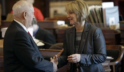 """FILE - In this Jan. 9, 2012 file photo Sen. Liz Mathis, right, D-Robins, greets Sen. Wally Horn, D-Cedar Rapids, left, at the Statehouse in Des Moines, Iowa. Mathis said Tuesday, April 29, 2014 that Secretary of State Matt Schultz' chief deputy Jim Gibbons was a """"no-show employee"""" for seven months before resigning in December 2012. She is requesting an audit into the arrangement that allowed Gibbons to keep a $126,000 annual salary after his job was eliminated. (AP Photo/Charlie Neibergall, File)"""