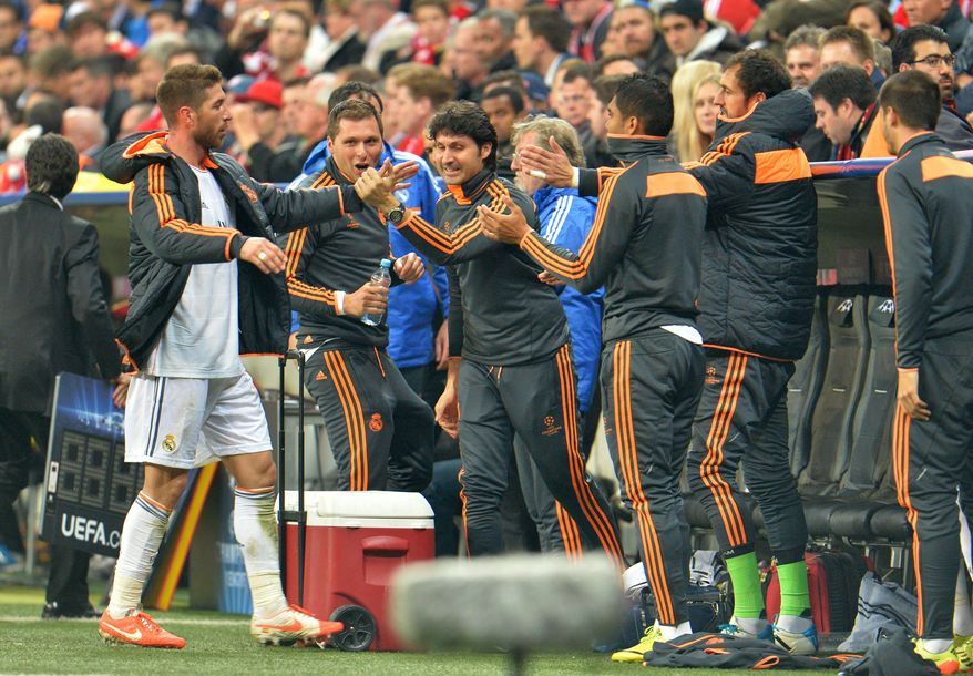 Real's Sergio Ramos shakes hands with teammates as he leaves the game during the Champions League semifinal second leg soccer match between Bayern Munich and Real Madrid at the Allianz Arena in Munich, southern Germany, Tuesday, April 29, 2014. (AP Photo/Kerstin Joensson)
