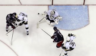 Pittsburgh Penguins' Marc-Andre Fleury, top right, makes a save as teammates Matt Niskanen (2), Olli Maatta (3), of Finland, Columbus Blue Jackets' Mark Letestu (55) and Blake Comeau (14) fight for position during the third of Game 6 of a first-round NHL playoff hockey series Monday, April 28, 2014, in Columbus, Ohio. The Penguins advance to the second round with their 4-3 win over the Blue Jackets. (AP Photo/Jay LaPrete)