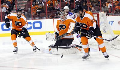 Philadelphia Flyers' Steve Mason, center, makes a save with Andrew MacDonald, left, and Mark Streit, right, of Switzerland, during the second period in Game 6 of an NHL hockey first-round playoff series against the New York Rangers, Tuesday, April 29, 2014, in Philadelphia. (AP Photo/Chris Szagola)
