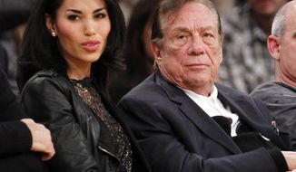** FILE ** In this Dec. 19, 2010, file photo, Los Angeles Clippers owner Donald Sterling, third right, sits with V. Stiviano, left, as  they watch the Clippers play the Los Angeles Lakers during an NBA preseason basketball game in Los Angeles. NBA commissioner Adam Silver announced Tuesday, April 29, 2014, that he is banning the owner for life from the Clippers organization over racist comments in recording. (AP Photo/Danny Moloshok, File)