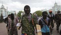 Masked pro-Russian activists march to storm an administration building in the center of Luhansk, Ukraine, one of the largest cities in Ukraine's troubled east, Tuesday, April 29, 2014, as demonstrators demand greater autonomy for Ukraine's regions. The action on Tuesday further raises tensions in the east, where insurgents have seized control of police stations and other government buildings in at least 10 cities and towns. (AP Photo/Alexander Zemlianichenko)