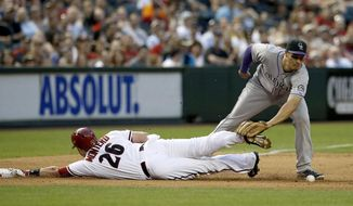 Arizona Diamondbacks' Miguel Montero (26) dives safely into third base as Colorado Rockies' Nolan Arenado is unable to catch the ball during the second inning of a baseball game on Tuesday, April 29, 2014, in Phoenix. (AP Photo/Ross D. Franklin)