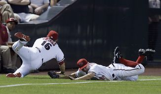 Arizona Diamondbacks' Chris Owings (16) makes a diving catch on a ball hit by Colorado Rockies' Jordan Pacheco as Diamondbacks' Tony Campana, right, also dives for the ball, and the two barely avoid colliding during the eighth inning of a baseball game Tuesday, April 29, 2014, in Phoenix. (AP Photo/Ross D. Franklin)