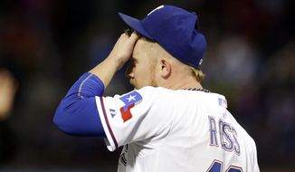 Texas Rangers starting pitcher Robbie Ross wipes his forehead after giving up a double to Oakland Athletics' Yoenis Cespedes in the fourth inning of a baseball game, Wednesday, April 30, 2014, in Arlington, Texas. (AP Photo/Tony Gutierrez)