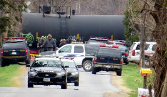 In this Sunday, April 27, 2014 photo, authorities investigate a fatal train accident that killed a married couple who were standing on the tracks in Verona, N.Y. Authorities ruled the incident a murder-suicide after they determined that Earl Myatt Jr. decided to drive Mary, his wife of 42 years, to the railroad crossing, and stand with her in the path of an oncoming freight train. Relatives have said he became despondent after she suffered a brain aneurysm in January 2014 that left her with a drastically diminished mental capacity. (AP Photo/Observer-Dispatch, Philip A. Vanno)