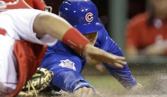 Chicago Cubs' Anthony Rizzo, right, tags home plate ahead of the tag by Cincinnati Reds catcher Brayan Pena in the fifth inning of a baseball game on Wednesday, April 30, 2014, in Cincinnati. Rizzo scored on a sacrifice fly by Nate Schierholtz. (AP Photo)