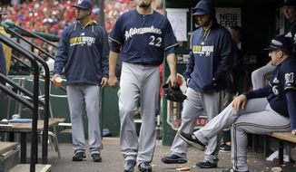 Milwaukee Brewers' Matt Garza (22) walks in the dugout after leaving a baseball game against the St. Louis Cardinals due to an injury during the fourth inning Wednesday, April 30, 2014, in St. Louis. (AP Photo/Jeff Roberson)