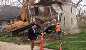 Bill Pulte Jr. walks in front of a Pontiac house being demolished by Pulte's nonprofit Detroit Blight Authority on Wednesday, April 30, 2014. (AP Photo/Detroit Free Press, Bill Laitner)