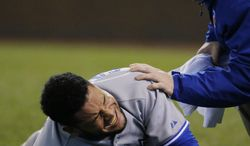 A team trainer comes to the aid of Toronto Blue Jays' Melky Cabrera after Cabrera was hit by a pitch from Kansas City Royals reliever Danny Duffy during the sixth inning of a baseball game at Kauffman Stadium in Kansas City, Mo., Wednesday, April 30, 2014. (AP Photo/Orlin Wagner)