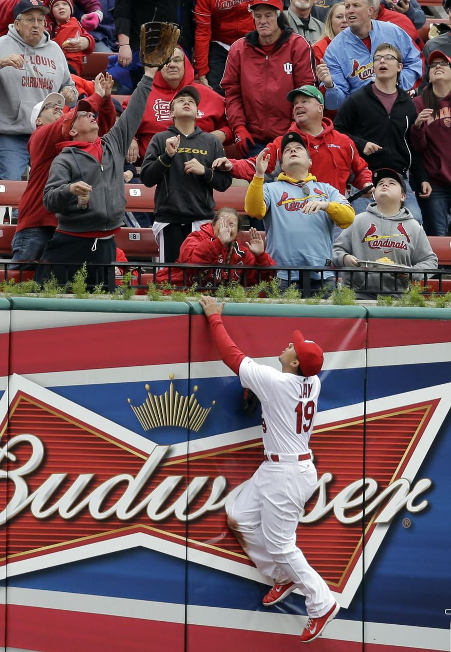 St. Louis Cardinals center fielder Jon Jay climbs the outfield wall looking for a two-run home run hit by Milwaukee Brewers' Mark Reynolds during the second inning of a baseball game Wednesday, April 30, 2014, in St. Louis. (AP Photo/Jeff Roberson)